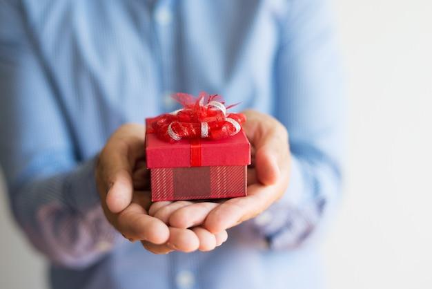 Nahaufnahme des unerkennbaren mannes, der kleine geschenke in den händen hält