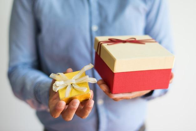 Nahaufnahme des unerkennbaren mannes, der zwei geschenkboxen hält