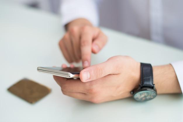 Nahaufnahme des unerkennbaren mannes mit der armbanduhr unter verwendung des smartphone
