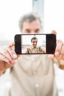 Nahaufnahme des unscharfen älteren mannes, der selfie mit smartphone nimmt