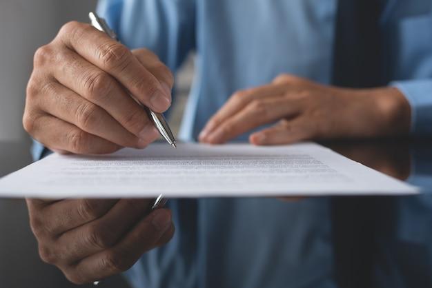 Nahaufnahme des unternehmers, der offiziellen vertrag mit einem stift auf bürotisch unterzeichnet