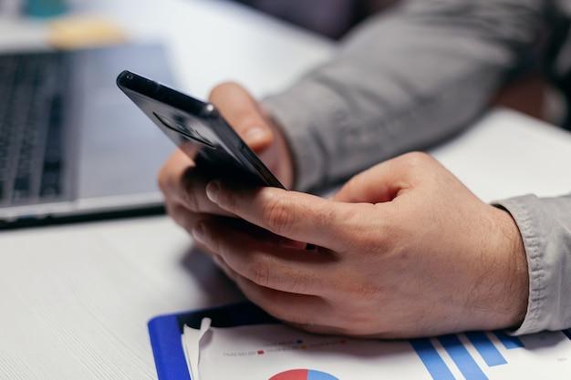 Nahaufnahme des unternehmers mit smartphone im innenbereich. geschäftsmann, der seine zelle verwendet, um eine sms zu senden, während er spät nachts im büro arbeitet, um eine frist zu beenden.