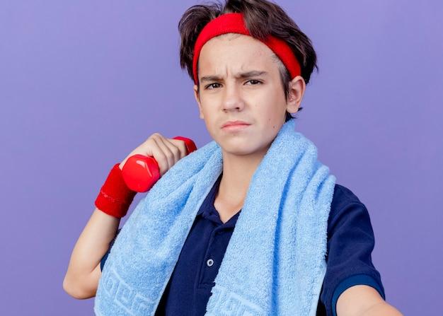 Nahaufnahme des unzufriedenen jungen gutaussehenden sportlichen jungen, der stirnband und armbänder mit zahnspangen und handtuch um hals hält, die hantel betrachten, die front lokalisiert auf lila wand hält
