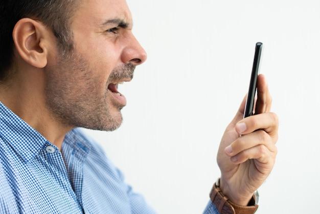 Nahaufnahme des verärgerten geschäftsmannes, der am smartphone schreit