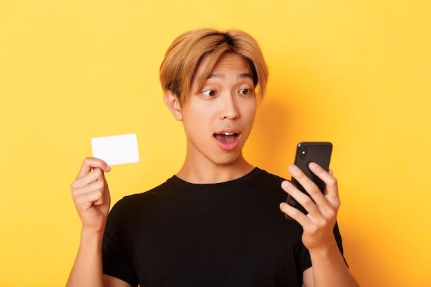 Nahaufnahme des verblüfften asiatischen kerls, der handy beim einkaufen online betrachtet und kreditkarte, gelbe wand zeigt