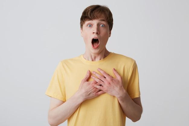 Nahaufnahme des verblüfften verängstigten jungen mannes mit geöffnetem mund trägt gelbes t-shirt