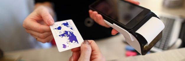 Nahaufnahme des verkäufers, der plastikkreditkarte vom kunden zur zahlung über terminalserver nimmt. codetastatur mit bildschirm zur information und überprüfung. modernes technologiekonzept