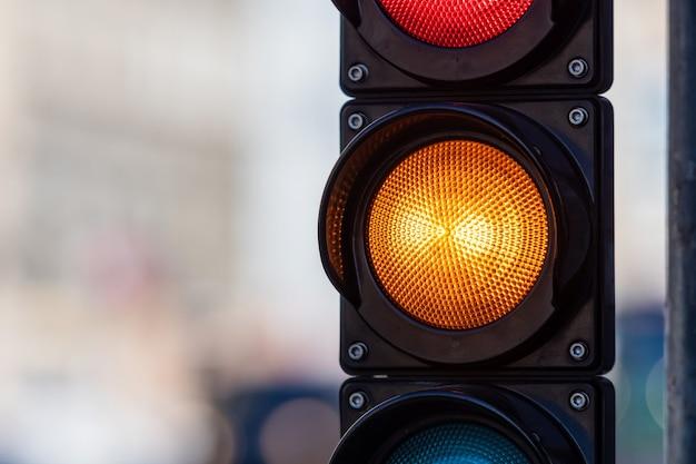 Nahaufnahme des verkehrssemaphors mit orangefarbenem licht auf defokussiertem stadtstraßenhintergrund mit kopienraum