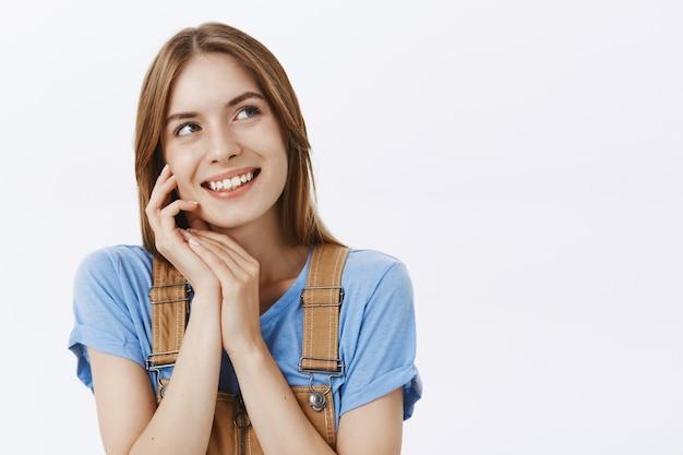 Nahaufnahme des verträumten schönen jungen mädchens, das lächelt, gesicht sanft berührt und obere rechte ecke schaut