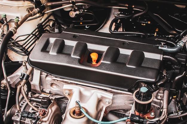 Nahaufnahme des vierzylinders des automotors in einem auto für wartungsservice.