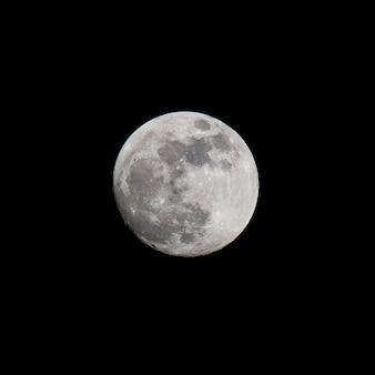 Nahaufnahme des vollmonds über dem dunklen schwarzen himmel in der nacht, aufgenommen am 26. oktober 2015