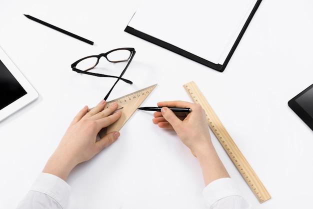 Nahaufnahme des weiblichen architekten die skizzen auf weißbuch zeichnend