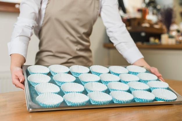 Nahaufnahme des weiblichen bäckers, der rostfreien behälter mit silbernen formen des kleinen kuchens backend hält