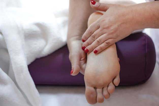 Nahaufnahme des weiblichen fußes in den händen eines masseurs entspannende fußmassage in einem spa-salon.