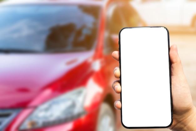 Nahaufnahme des weiblichen gebrauches ein smartphone und ein auto im vordergrund