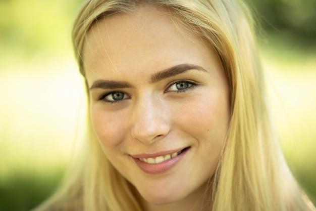 Nahaufnahme des weiblichen gesichts, lächelndes blondes mädchen in der natur
