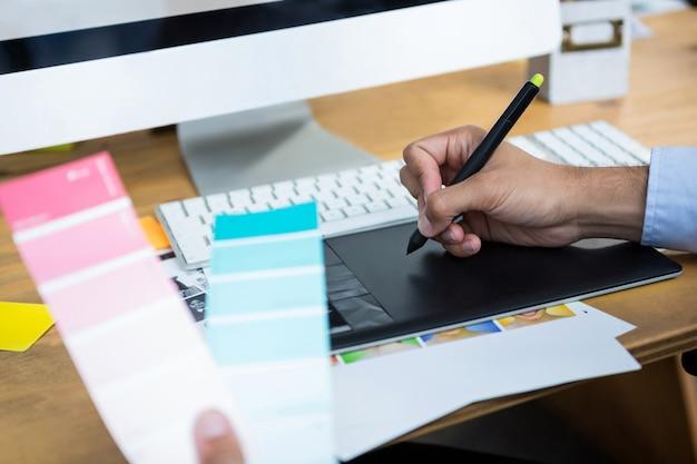 Nahaufnahme des weiblichen grafikdesigners, der am schreibtisch arbeitet