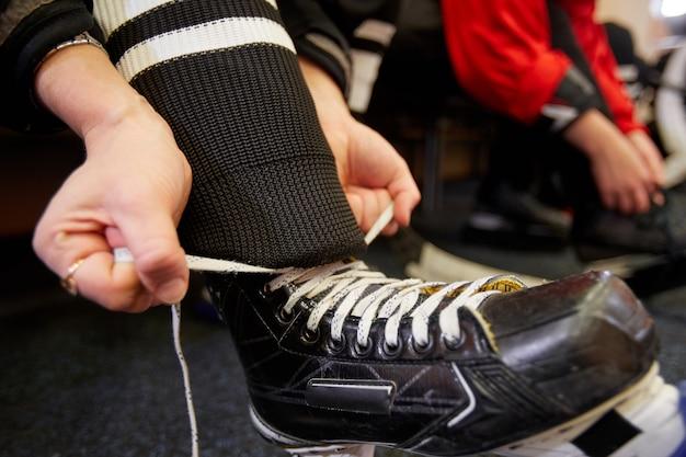 Nahaufnahme des weiblichen hockeyspielers, der ausrüstung anlegt