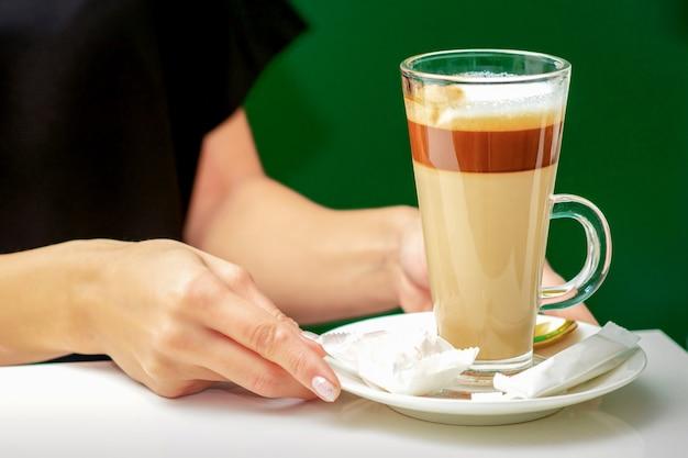Nahaufnahme des weiblichen kellners gibt tasse kaffee latte mit süßigkeiten im teller auf dem tisch