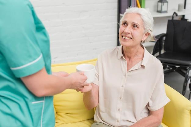 Nahaufnahme des weiblichen krankenschwesterumhüllungskaffees zur älteren frau
