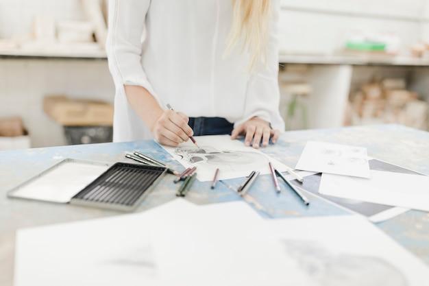 Nahaufnahme des weiblichen künstlers skelett auf papier mit bleistift auf tabelle skizzierend