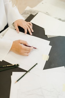 Nahaufnahme des weiblichen künstlers skizzend mit bleistift auf weißbuch mit bleistift