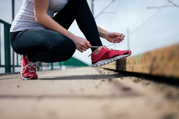 Nahaufnahme des weiblichen läufers spitze bindend.
