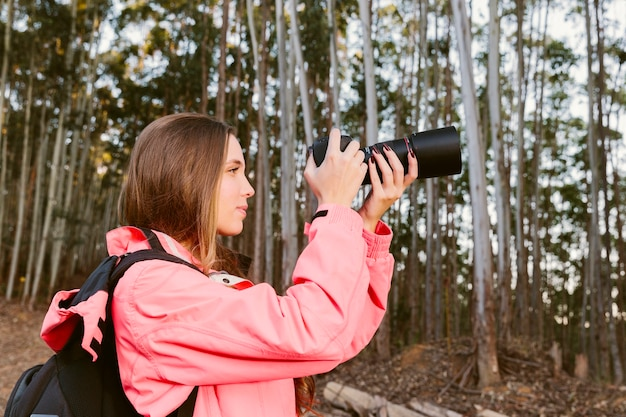 Nahaufnahme des weiblichen reisenden fotografierend im wald