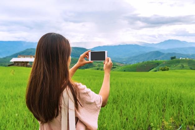 Nahaufnahme des weiblichen reisenden unter verwendung des smartphones machen ein foto an reisfeldterrassen