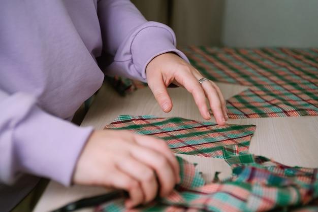 Nahaufnahme des weiblichen schneiders, der karierten stoff mit einem papiermuster herausschneidet, um ein hemd zu erkennen