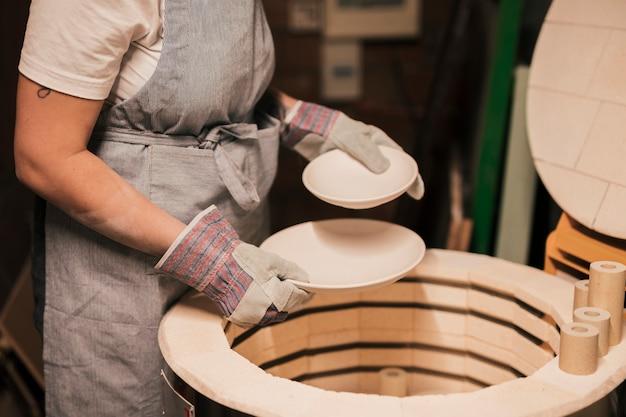 Nahaufnahme des weiblichen töpfers die keramischen platten vereinbarend