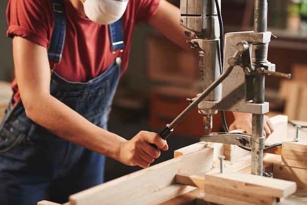 Nahaufnahme des weiblichen zimmermanns im denim-gesamtpresshebel auf der holzbearbeitungsmaschine während der verarbeitung von holzbrettern