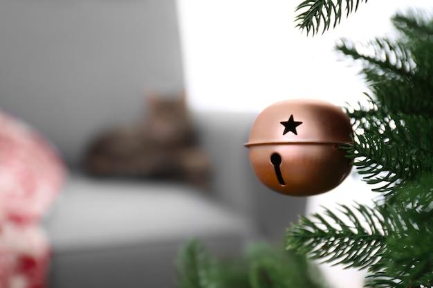 Nahaufnahme des weihnachtsbaums mit jingle bell auf verschwommener oberfläche