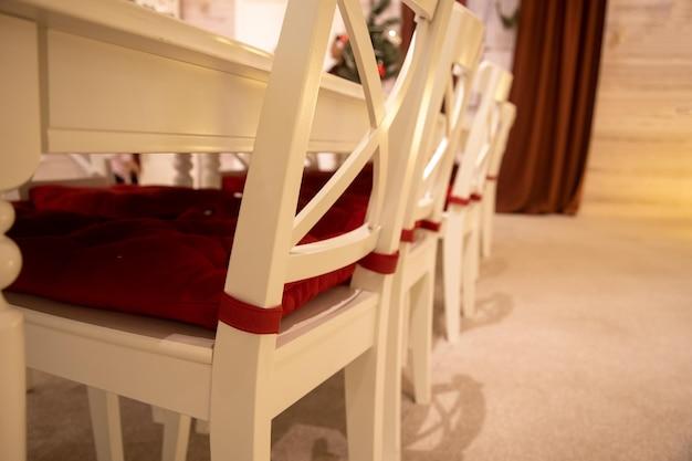 Nahaufnahme des weißen esstisches mit rotem kissen auf dem hintergrund des festlichen neujahrsinnenraums