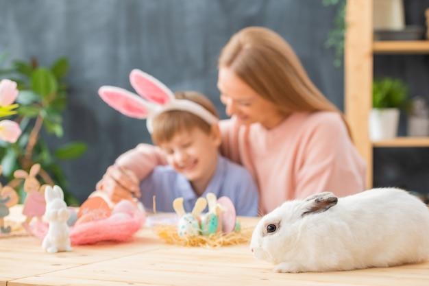 Nahaufnahme des weißen flauschigen kaninchens, das auf holztisch mit osterdekorationen liegt, mutter umarmt sohn