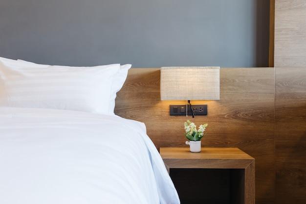 Nahaufnahme des weißen kissens auf bettdekoration mit heller lampe im hotelschlafzimmerinnenraum.