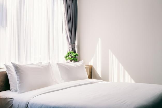 Nahaufnahme des weißen kissens auf bettdekoration mit heller lampe und grünem baum