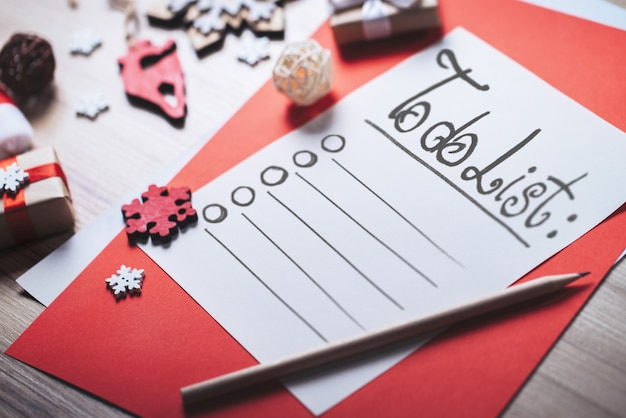 Nahaufnahme des weißen stücks papier mit zu tun liste und feiertagsdekorationen auf hölzernem schreibtisch