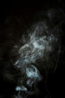 Nahaufnahme des weißen wispy rauches auf schwarzem hintergrund