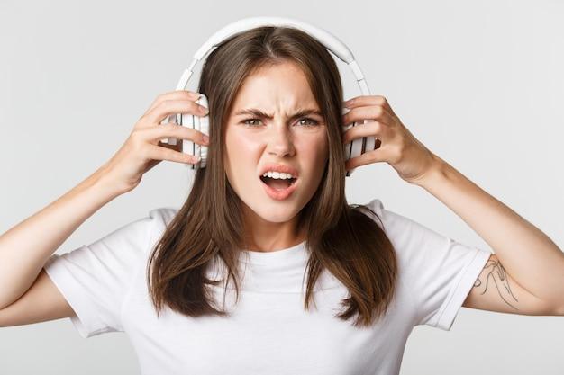 Nahaufnahme des wütenden und selbstbewussten jungen mädchens, das sich über schreckliche musik in drahtlosen kopfhörern beschwert
