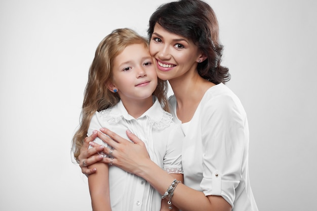 Nahaufnahme des wunderbaren familienpaares: schöne mutter und ihre kleine nette tochter. sie sind sehr glücklich mit einem hübschen lächeln. sie tragen weiße t-shirts.