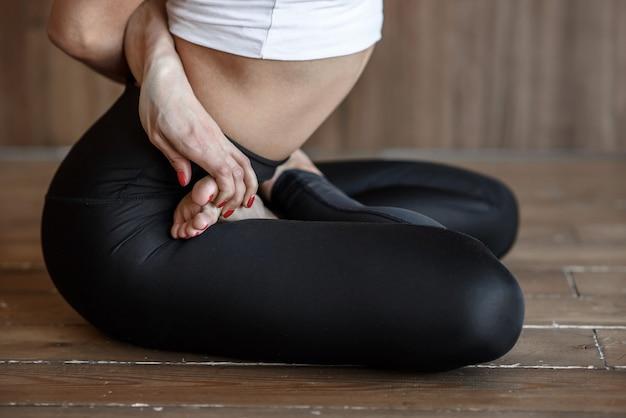Nahaufnahme des yoga-körperteils der trainerfrau-person, das auf boden in der lotussitzposition sitzt, die yoga-übung praktiziert