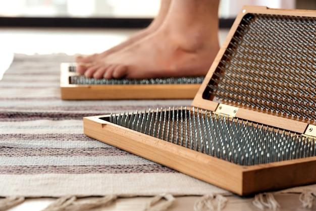 Nahaufnahme des yoga-mannes stehen auf sadhu brett mit scharfen nägeln