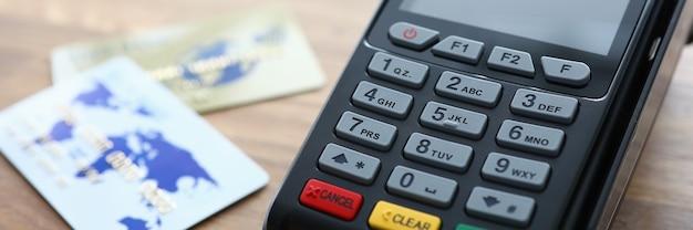 Nahaufnahme des zahlungsterminals und der kreditkarten auf holztisch. moderner kartenleser zum online-bezahlen. kaufen und verkaufen sie produkte oder dienstleistungen. technologiekonzept