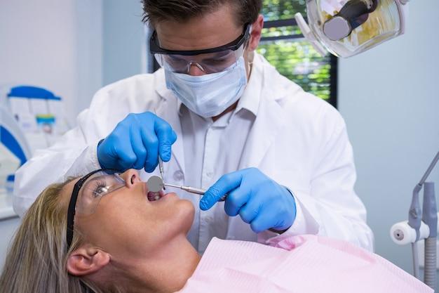 Nahaufnahme des zahnarztes, der frau untersucht