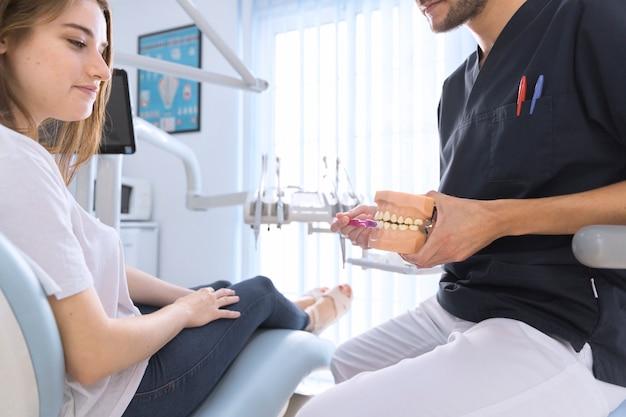 Nahaufnahme des zahnarztes, der zahnbürste auf zahnmodell in der zahnmedizinischen klinik verwendet