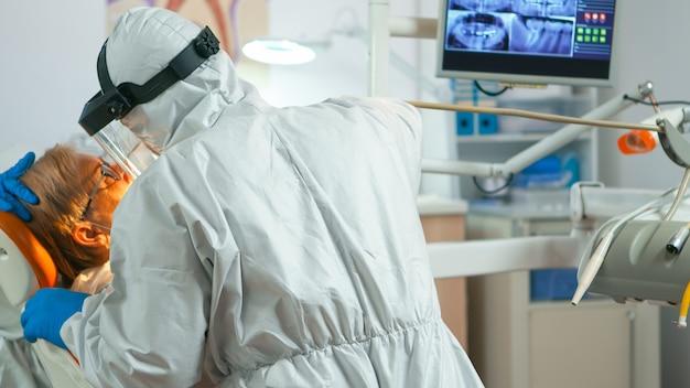 Nahaufnahme des zahnarztes im overall mit bohrmaschine zur untersuchung des patienten während der globalen pandemie. ärzteteam mit schutzanzug, gesichtsschutz, maske, handschuhen im stomatologischen büro