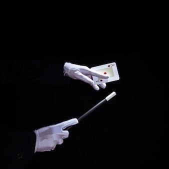 Nahaufnahme des zauberers trick auf spielkarte mit magischem stab durchführend
