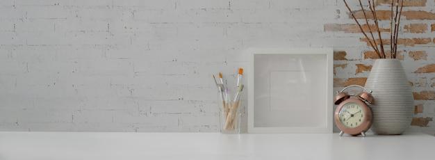 Nahaufnahme des zeitgenössischen arbeitsbereichs mit modellrahmen, malwerkzeugen, dekorationen und kopierraum