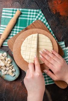 Nahaufnahme des zubereitungsprozesses von dushbere-suppenknödeln schneidebrett nudelholz auf halb gefaltetem grünem handtuch auf dunkler oberfläche